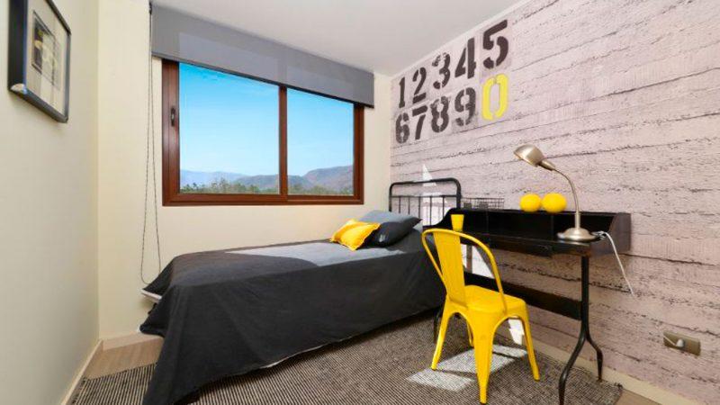 dormitorio con cama y silla